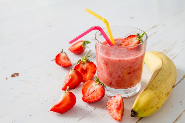 A straweberry banana smoothie in a class with straws and a banana and strawberries surrounding it