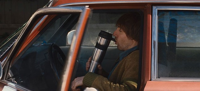 Guy from cabin in the woods smoking out of a coffee cup bong in his car