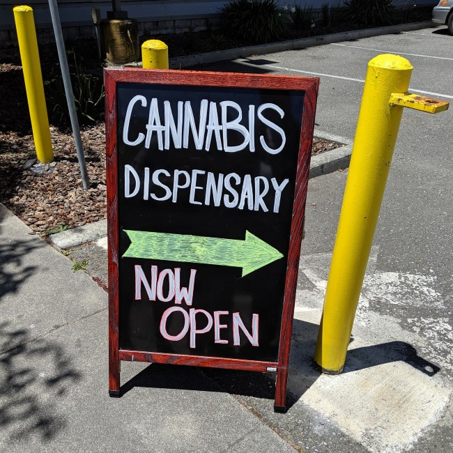 Sign saying cannabis dispensary now open